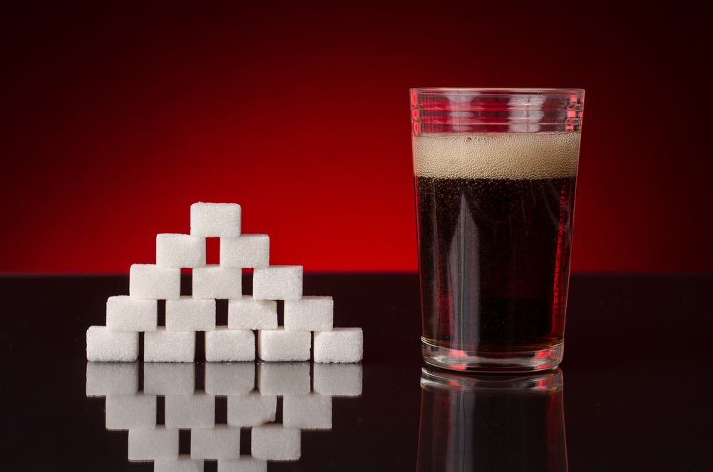Glass of soda and stack of sugar cubes