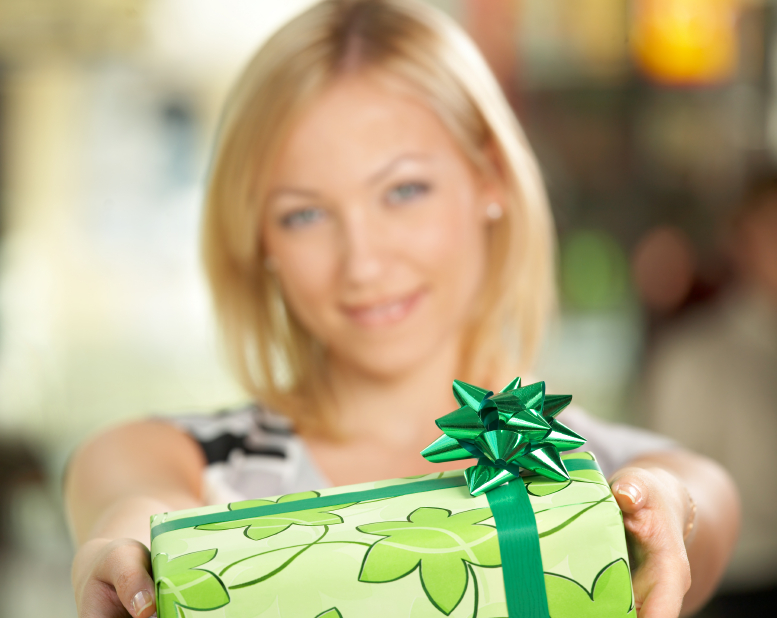 The attractive girl smiles and gives a gift in packing