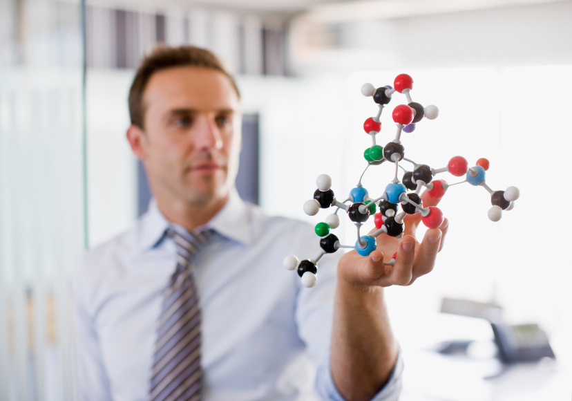 Businessman examines a free radical molecule representation
