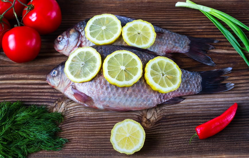 crude fish with a lemon, tomatoes, pepper, green onions and fennel on a brown wooden background