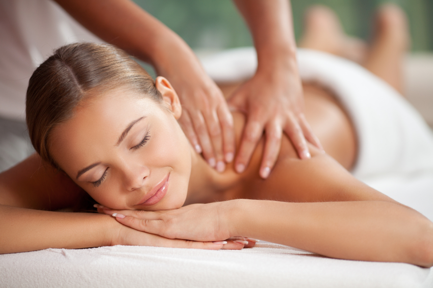 Young happy woman receiving shoulder massage at spa and beauty salon