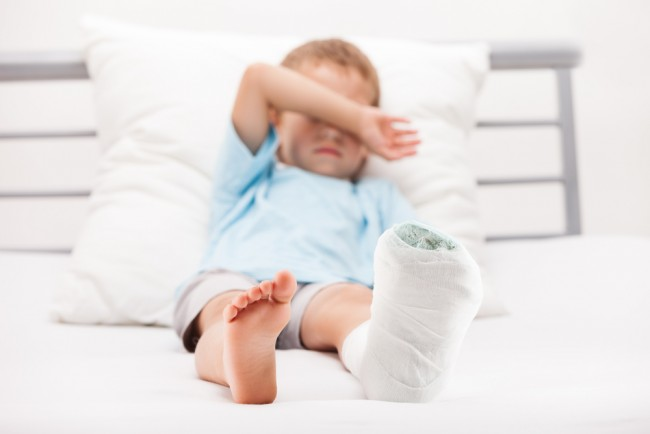 Small boy with a plaster bandage on his leg.