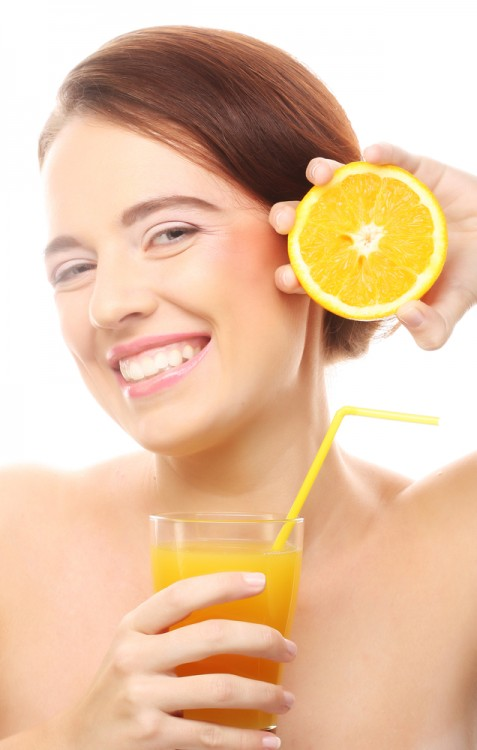 Woman holding an orange and a glass of orange juice in her hands.