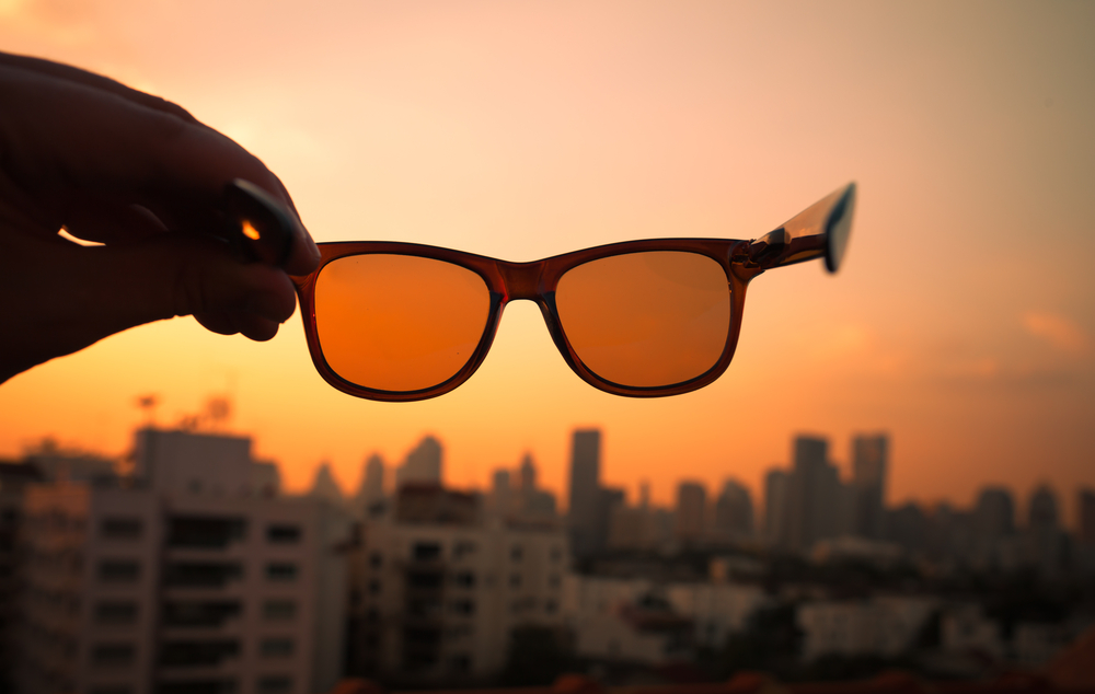 Woman holding orange colored glases