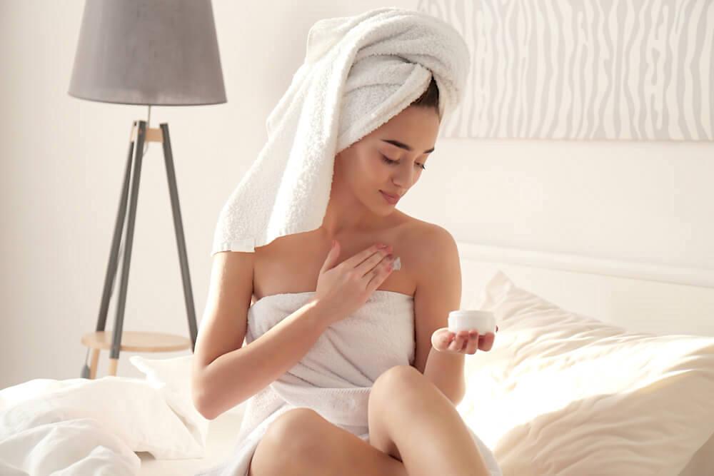 Woman applying moisturiser to body