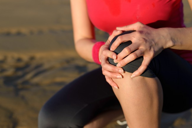 Woman suffering from joint pain while jogging.