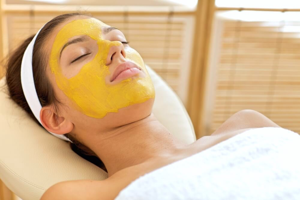Calm woman relaxing with turmeric facial mask