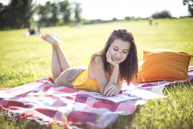 Young woman reading a magazine in the park.