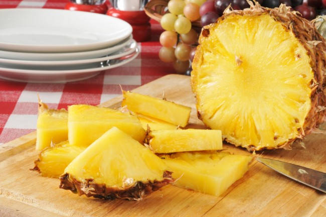 Sliced pineapples on a wooden board