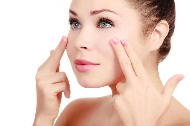 Young woman applying anti-aging products.