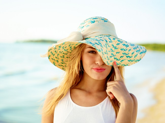 Beautiful woman wearing a hat in a beach