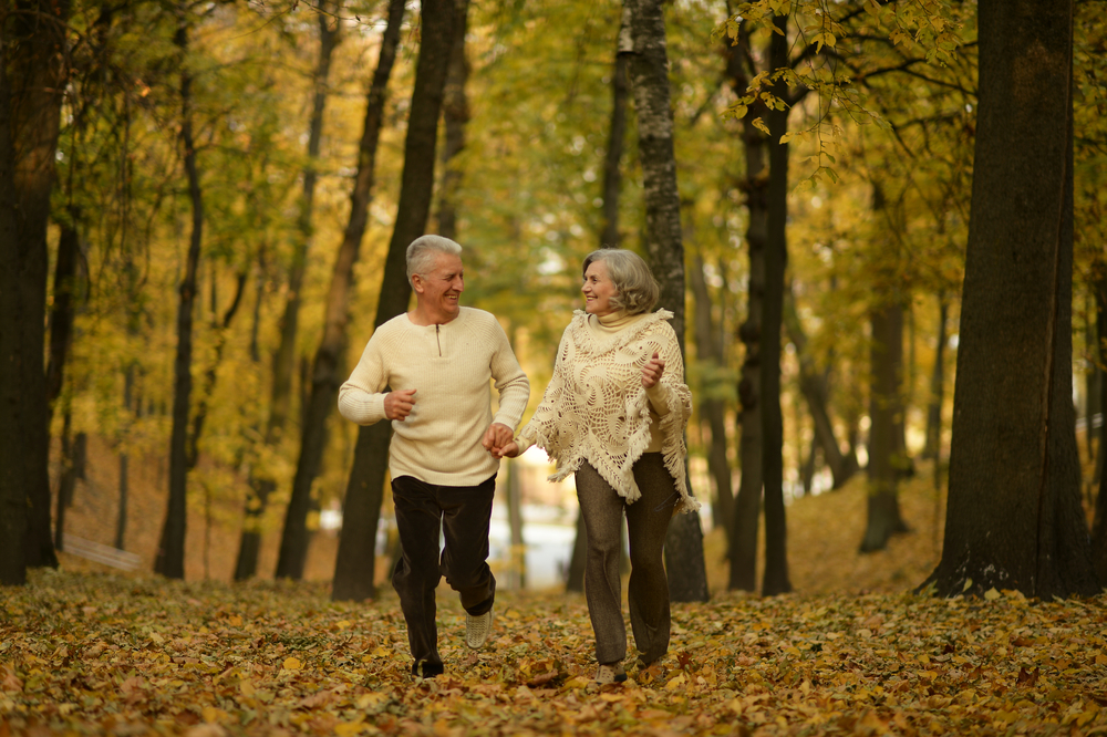 Mature couple jogging in the woods during fall.