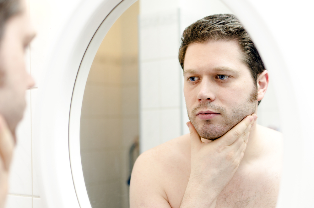 Man looking at his skin in the mirror.