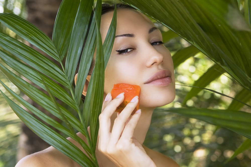 Woman holding a papaya on her cheek.