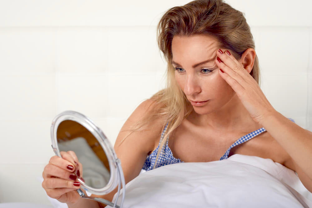 Woman checking her wrinkles in a handheld mirror
