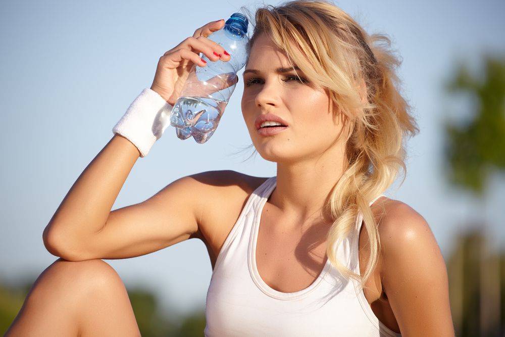Woman sweating and drinking water
