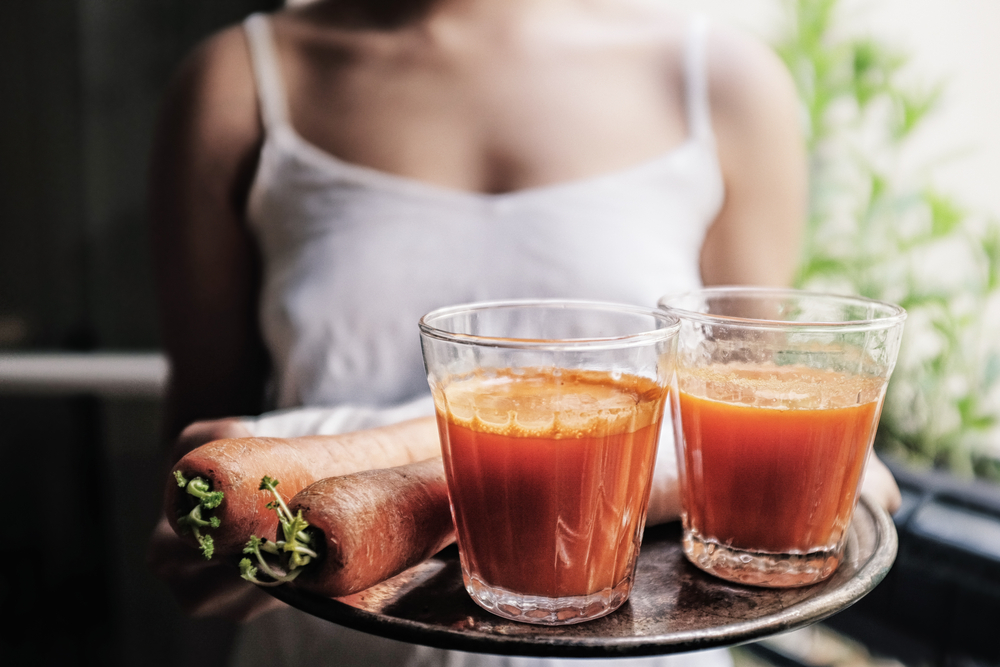 Woman drinking carrot juice