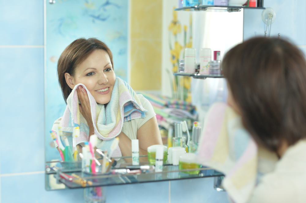 woman with good skin looking at herself in the mirror