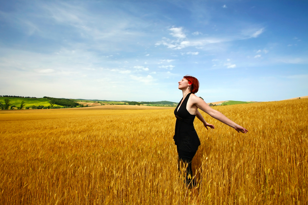 Woman spreading arms out in cereal field
