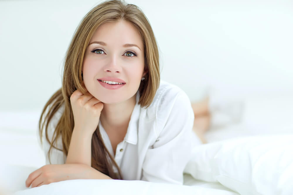 Smiling woman in white on bed