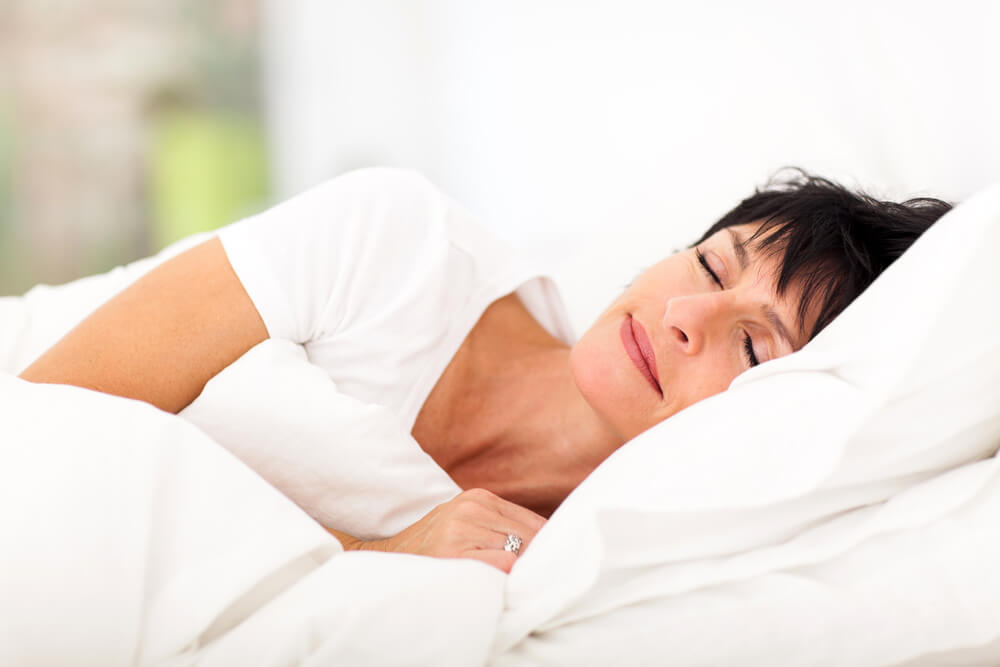 Woman sleeping on white bed