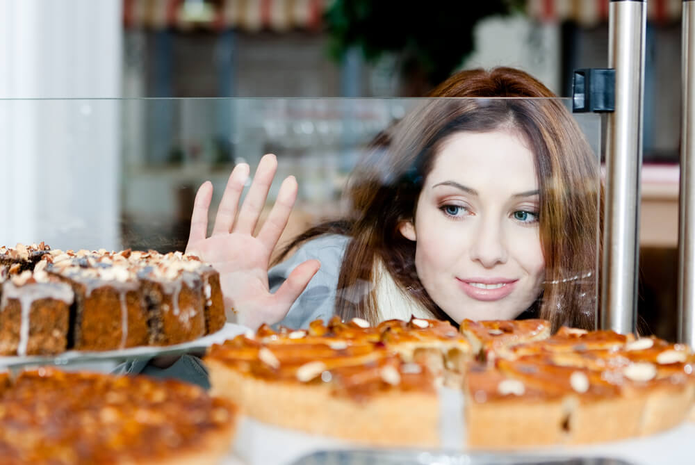 Woman looking forlornly at cakes in a shop