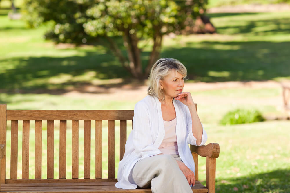 senior woman sitting on park bench