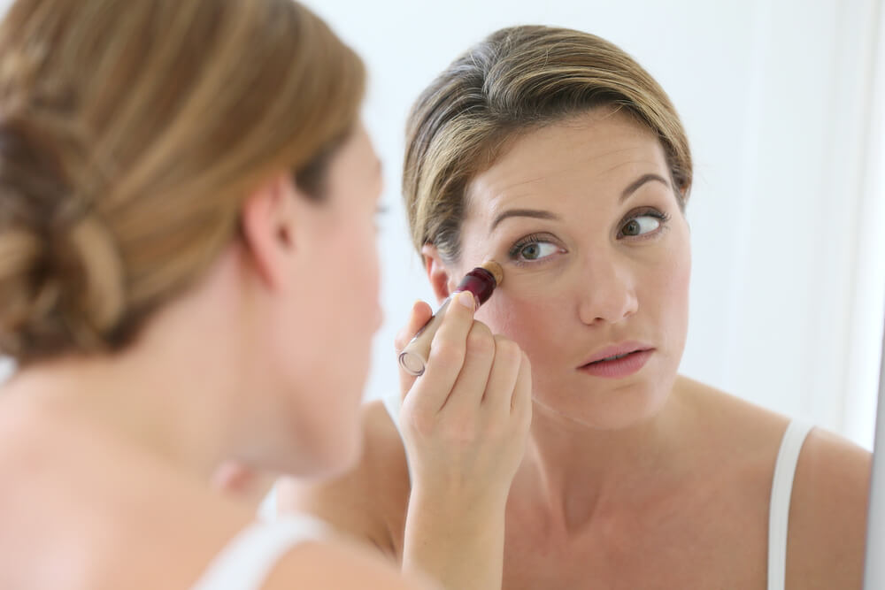 Woman trying to conceal her dark circles