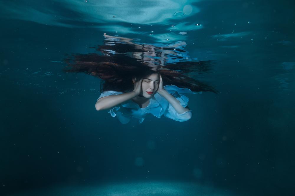 Woman in water closing her ears