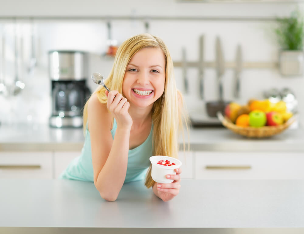 Smiling woman eating yogurt in kitchen