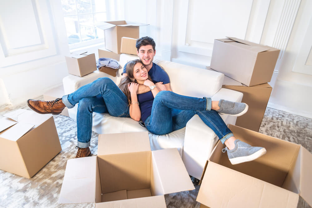 Couple moving in together with boxes all around