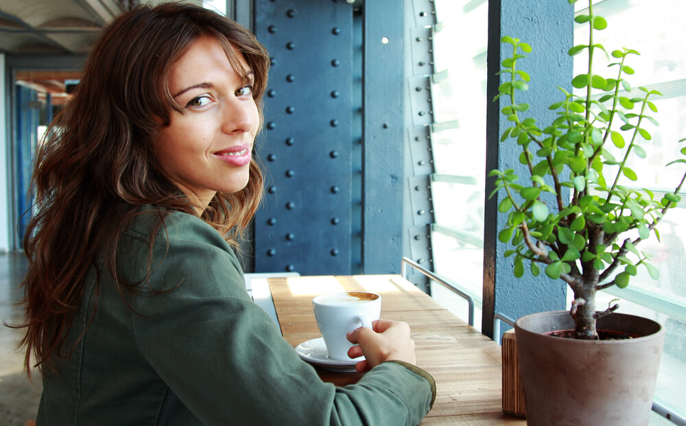 Woman looking over her shoulder with a cup of coffee
