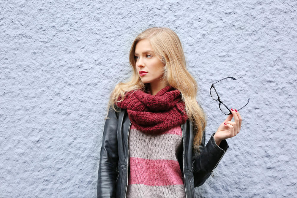Woman with scarf holding her glasses