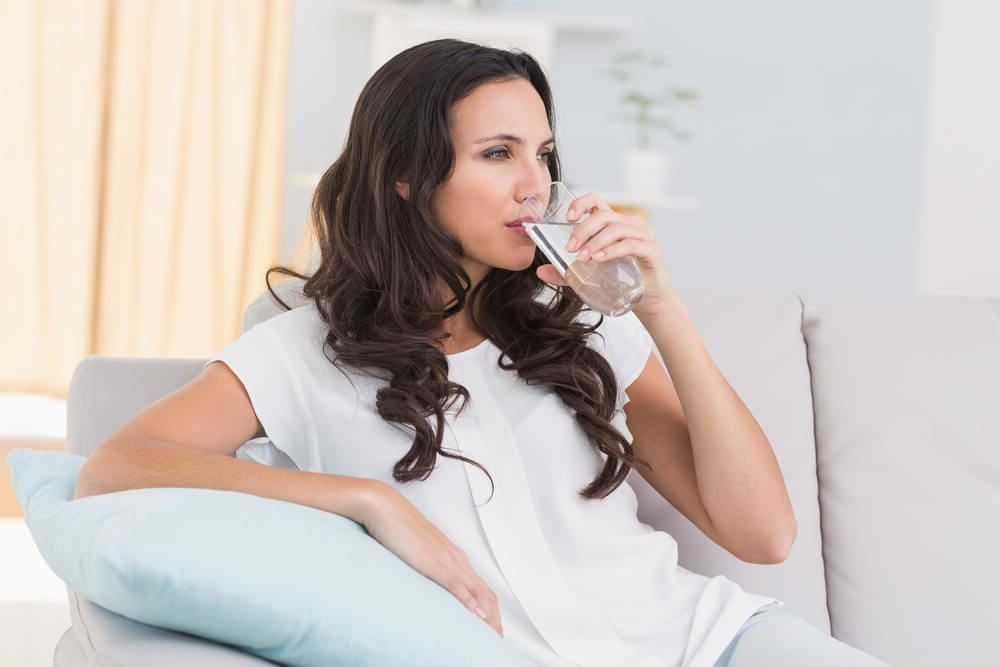 Woman drinking a glass of sparkling water at home
