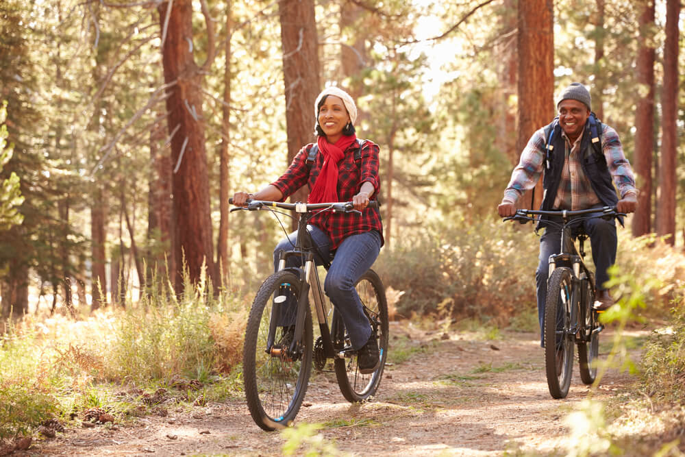 senior couple biking through fall woodlands