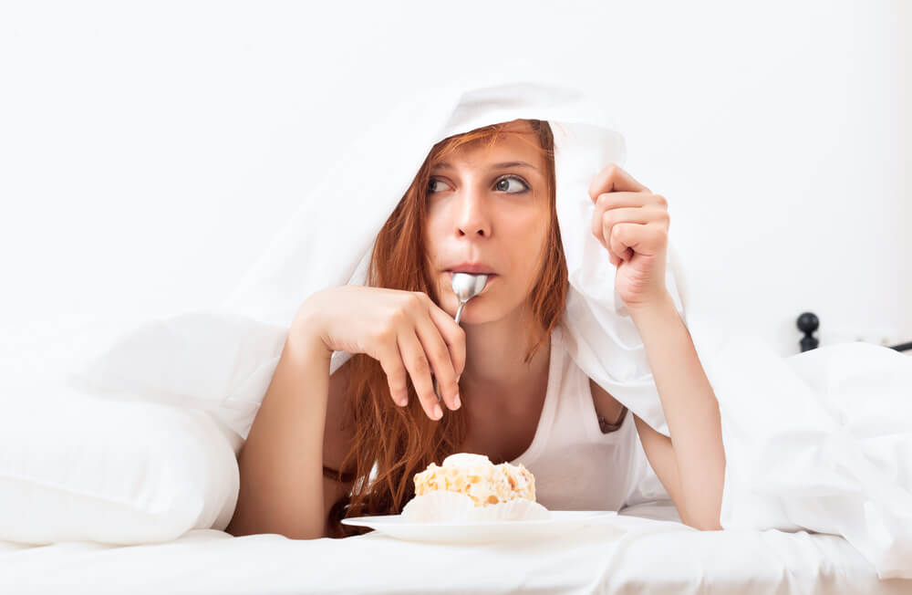 woman eating ice cream under bed sheets