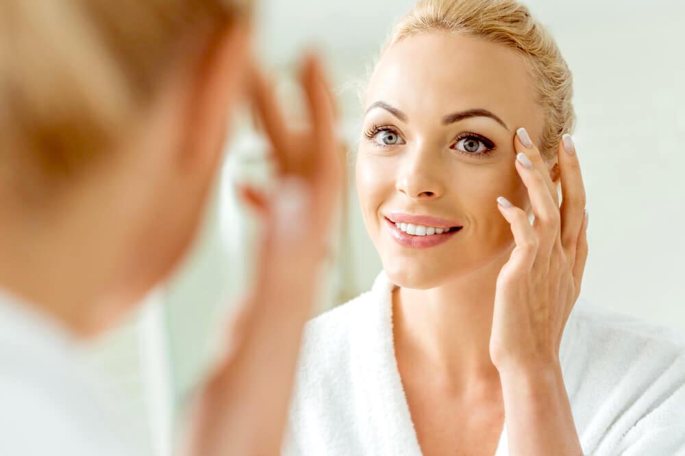 woman touching the skin around her eyes