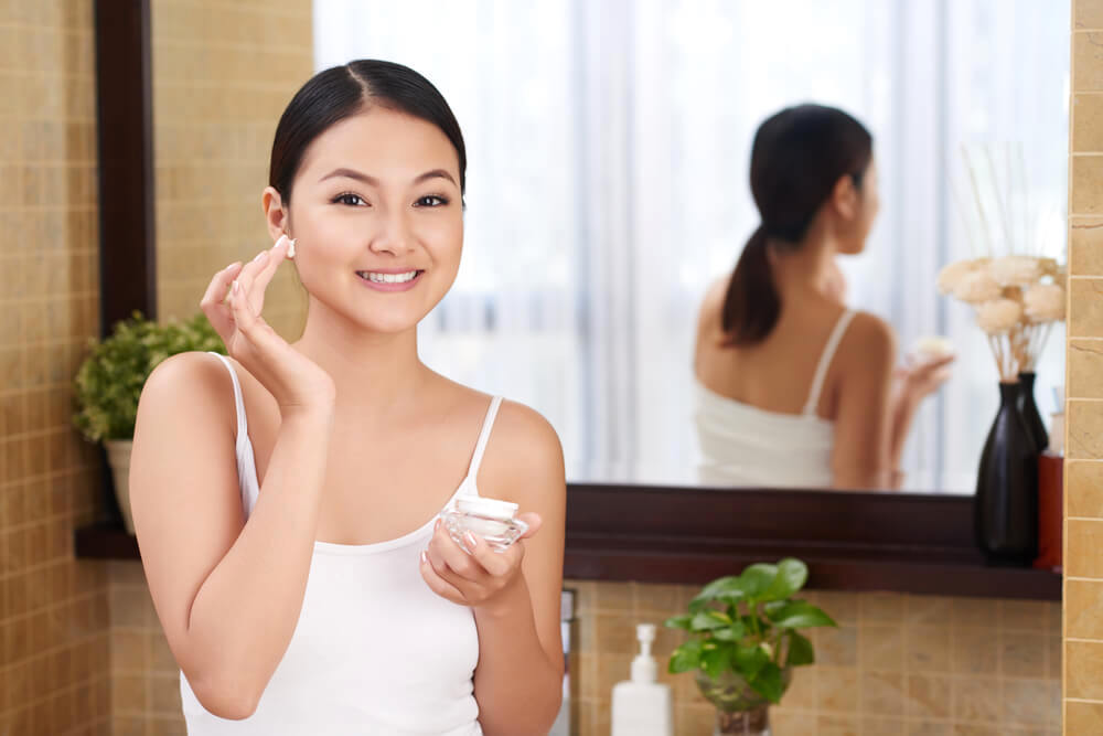 woman applying face moisturizer