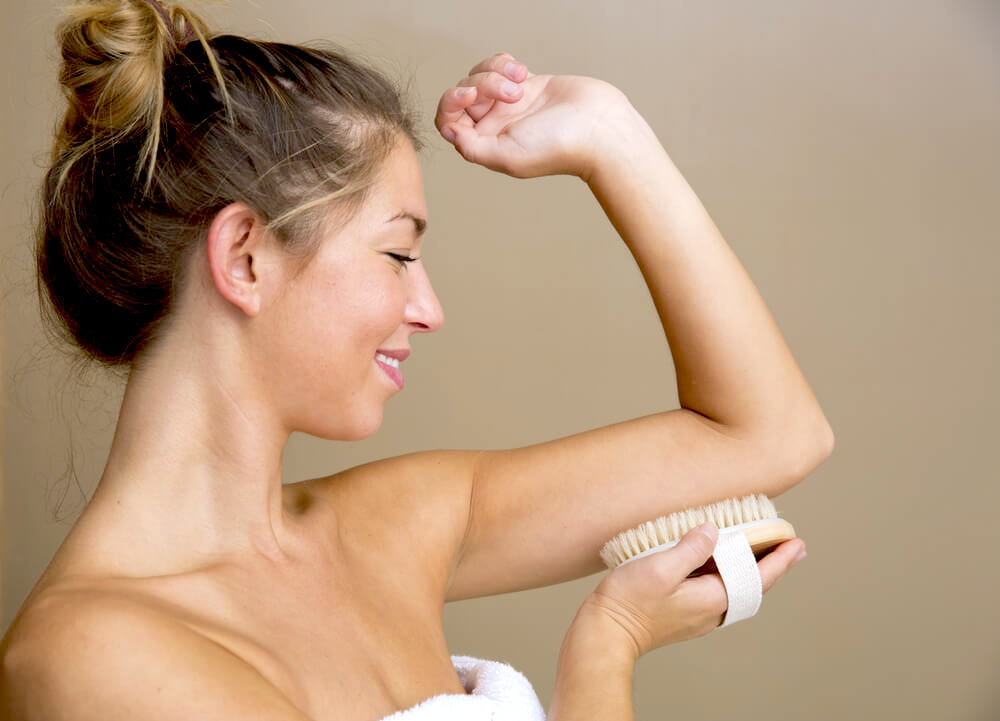Woman dry brushing her under arm