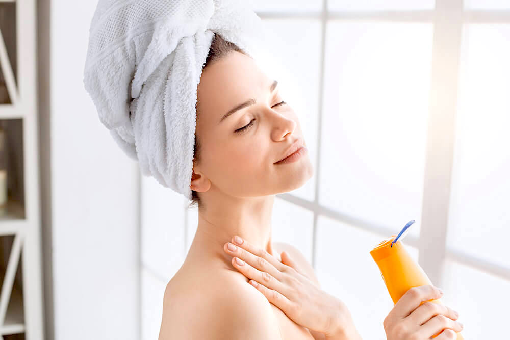 Woman applying sunscreen to the neck