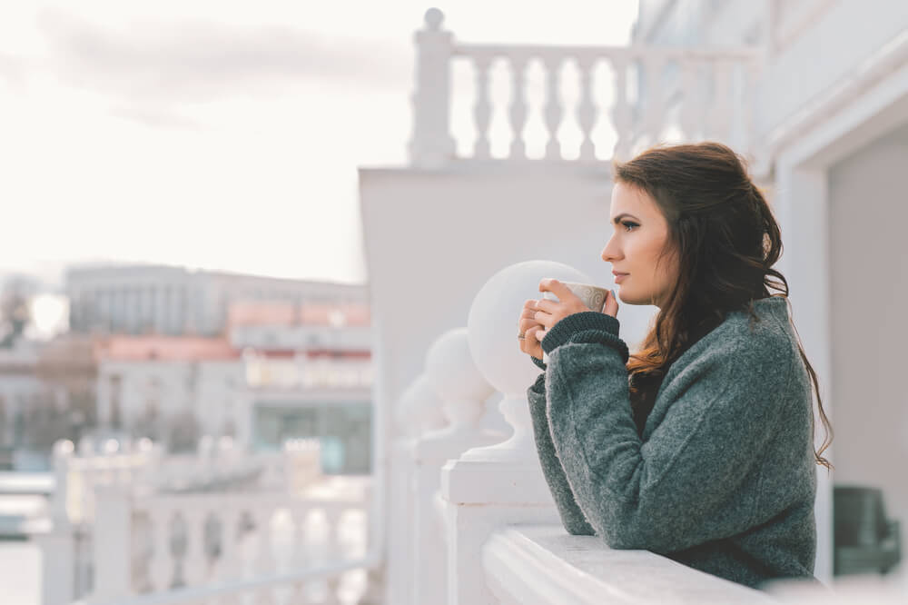 Young woman in long jumper drinking hot tea on a cold winter's day, on the balcony