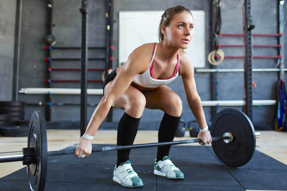 Strong athletic woman lifting up barbell