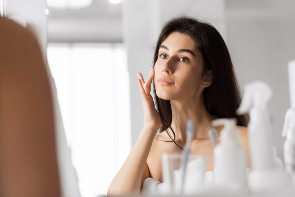 Woman applying skincare on face in front of bathroom mirror