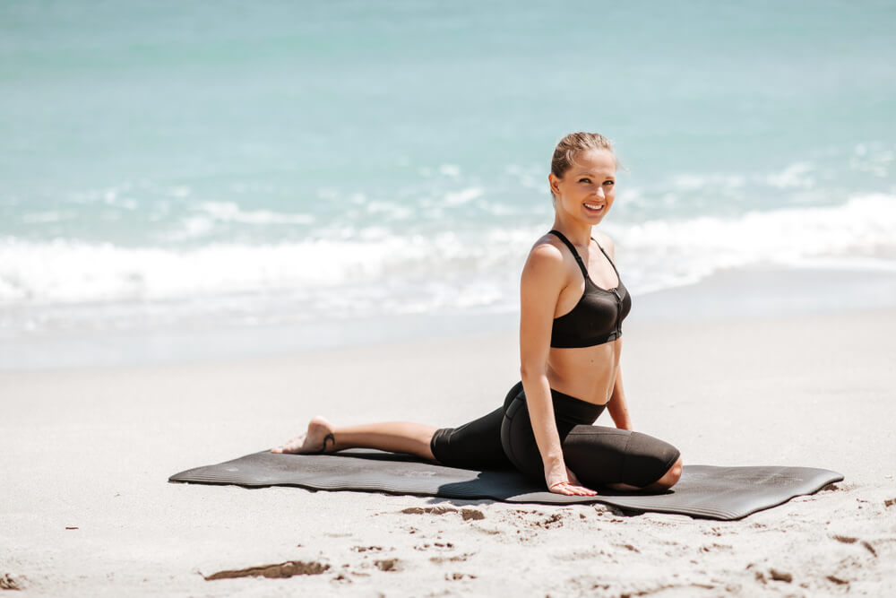 Smiling woman on a yoga mat on the beach