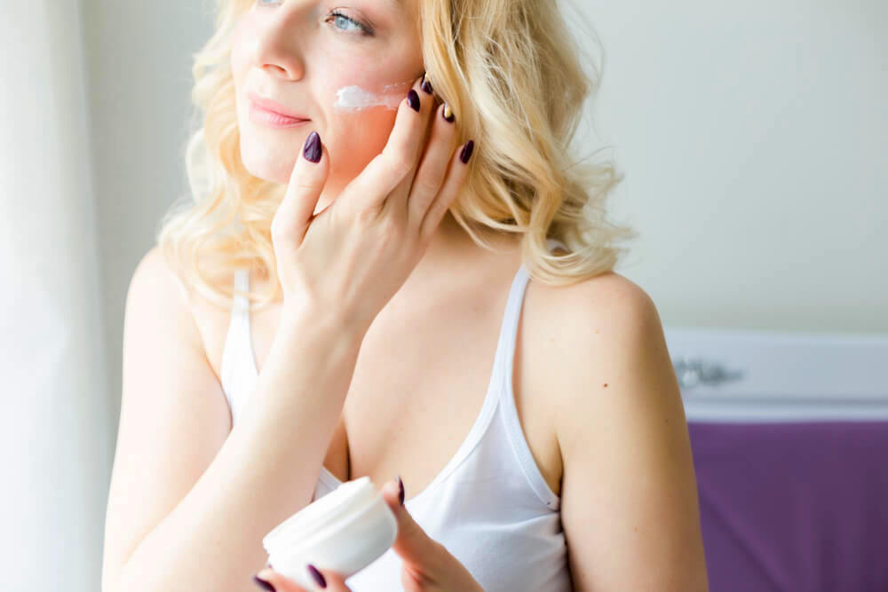 Beautiful gentle woman applying moisturizer in front of window