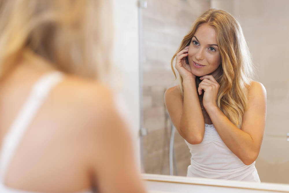 Smiling woman touching her face in front of bathroom mirror