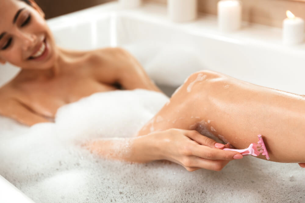 Smiling woman shaving leg in the bathtub